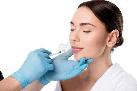 doctor in latex gloves giving lip injection with syringe to attractive woman isolated on white