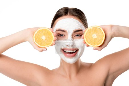 beautiful smiling woman with facial skin care mask holding oranges and looking at camera isolated on white