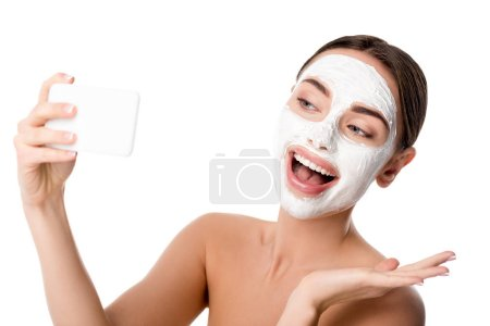 happy woman with facial skin care mask taking selfie on smartphone isolated on white