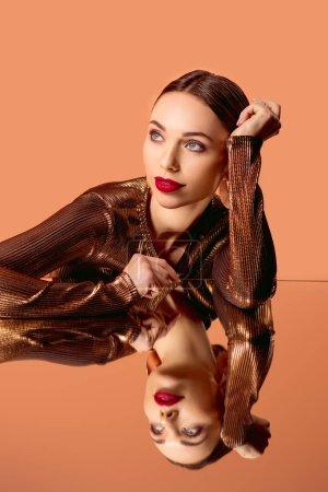 Photo pour Belle femme en vêtements dorés avec maquillage glamour et miroir reflet isolé sur orange - image libre de droit
