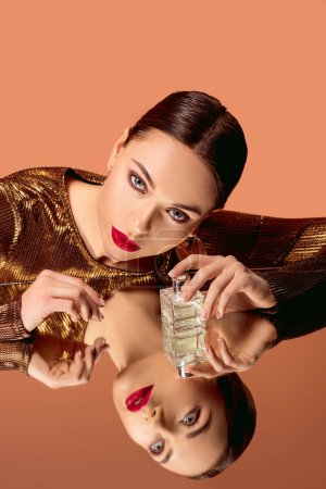 Photo for Attractive woman in golden clothes with glamorous makeup, perfume bottle and mirror reflection posing isolated on orange - Royalty Free Image