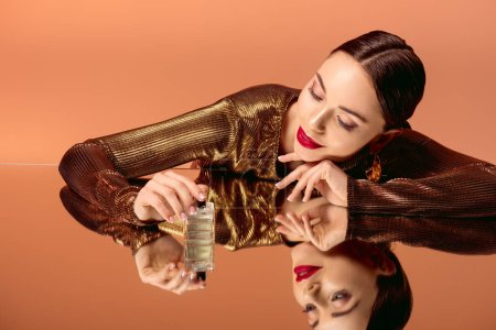 Photo for Beautiful smiling woman in golden clothes with glamorous makeup, perfume bottle and mirror reflection posing isolated on orange - Royalty Free Image