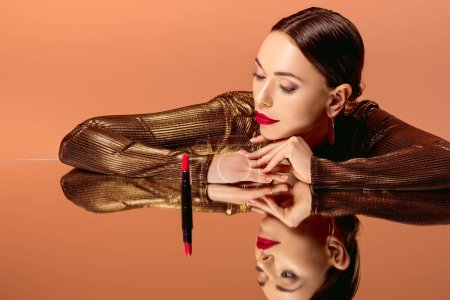 attractive woman in golden clothes with glamorous makeup, mirror reflection and red lipstick posing isolated on orange
