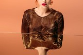 cropped view of woman in golden clothes with red lips and mirror reflection isolated on orange