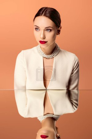Photo pour Belle femme glamour en collier de perles avec miroir reflet isolé sur orange - image libre de droit