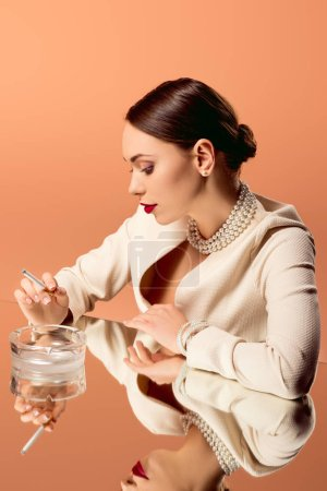 Photo for Woman in pearl necklace with mirror reflection holding cigarette over ashtray isolated on orange - Royalty Free Image