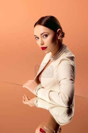 beautiful glamorous woman in pearl necklace with mirror reflection looking at camera isolated on orange