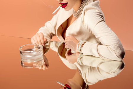 Photo for Cropped view of woman in pearl necklace with mirror reflection smoking cigarette isolated on orange - Royalty Free Image