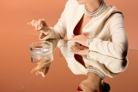 cropped view of woman in pearl necklace with mirror reflection holding cigarette over ashtray isolated on orange