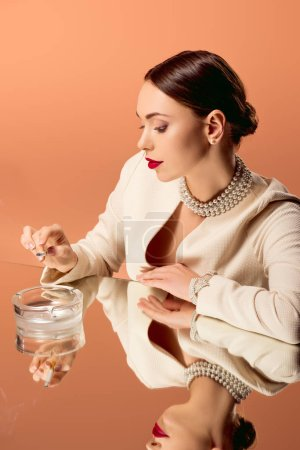 Photo for Beautiful glamorous woman in pearl necklace with mirror reflection holding cigarette over ashtray isolated on orange - Royalty Free Image