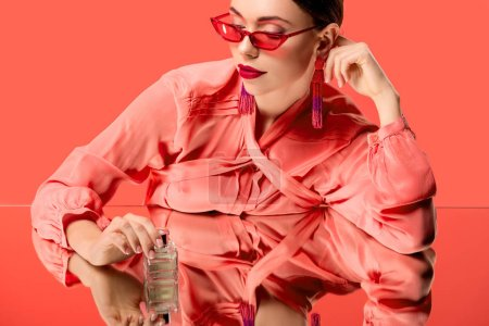 Photo for Stylish woman in blouse and red sunglasses posing with perfume bottle and mirror reflection isolated on living coral - Royalty Free Image