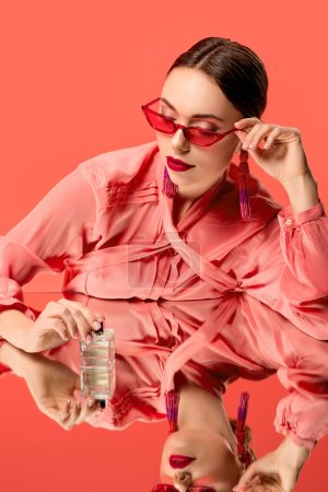 Photo for Glamorous woman in blouse and red sunglasses posing with perfume bottle and mirror reflection isolated on living coral - Royalty Free Image
