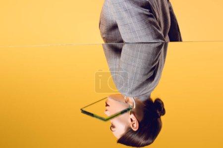 Photo pour Vue recadrée de femmes glamour en tenues avec reflet miroir isolé jaune - image libre de droit