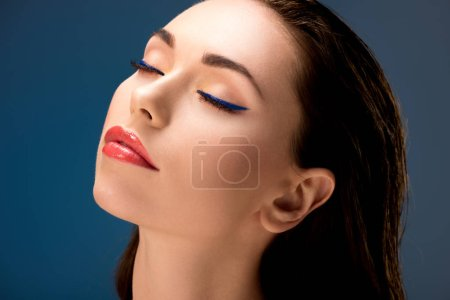 Photo for Portrait of beautiful woman with glamorous makeup and eyes closed isolated on blue - Royalty Free Image