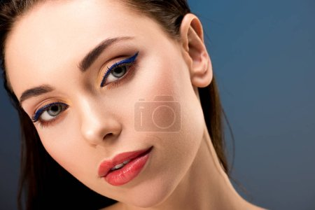 portrait of beautiful woman with glamorous makeup looking at camera isolated on blue