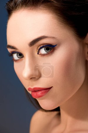 selective focus of beautiful woman with glamorous makeup looking at camera isolated on blue