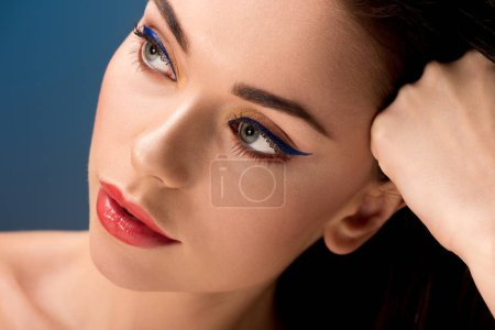 portrait of beautiful pensive woman with glamorous makeup isolated on blue