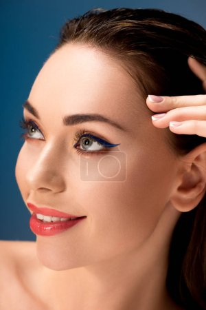 portrait of beautiful smiling woman with glamorous makeup touching face isolated on blue