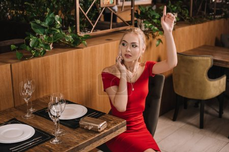 attractive woman in red dress sitting in restaurant and raising hand
