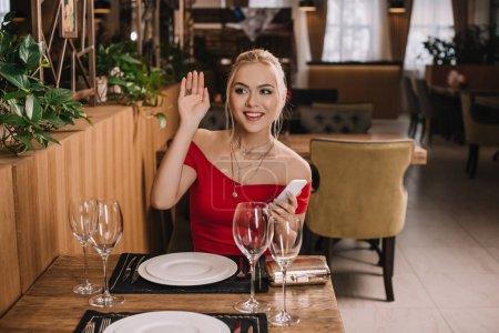 attractive woman in red dress sitting in restaurant waving hand