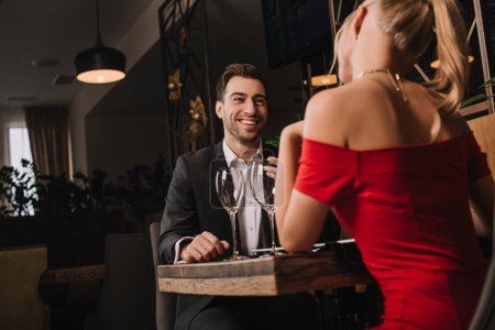 Photo pour Beau petit ami regardant petite amie en robe rouge pendant le dîner - image libre de droit