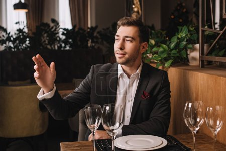 handsome man in suit waiting for girlfriend in restaurant and rising hand up