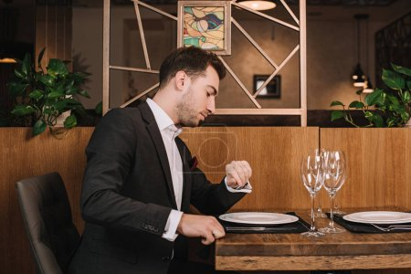 Photo for Handsome man in suit waiting for girlfriend in restaurant and looking at watch - Royalty Free Image