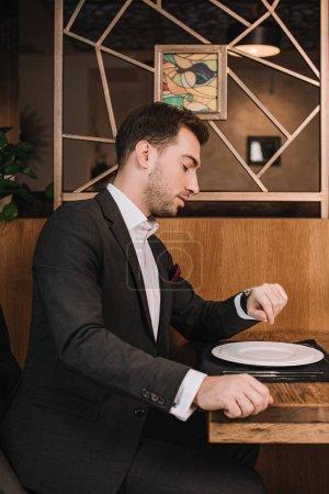 Photo pour Bel homme en costume regardant montre et assis dans le restaurant - image libre de droit