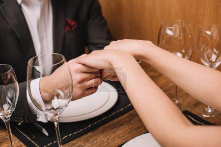 Photo pour Copain et copine tenant par la main en restaurant - image libre de droit