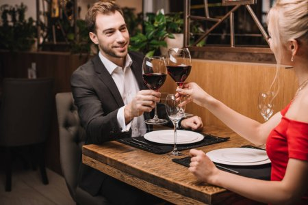 cheerful man toasting with red wine and smiling to girlfriend in restaurant