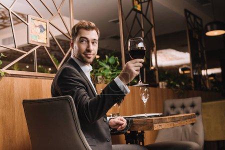 schöner Mann, der im Restaurant ein Glas mit Rotwein hält