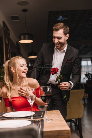 cheerful boyfriend giving red rose to surprised girlfriend in restaurant