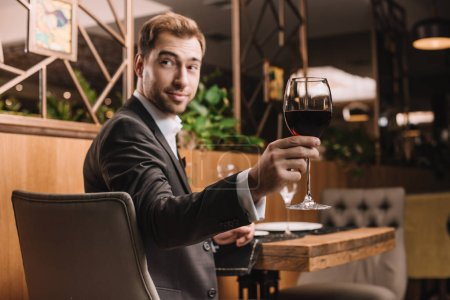 Photo for Selective focus of  glass with red wine in hand of handsome man - Royalty Free Image