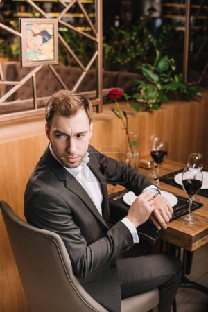 Photo for Handsome man touching watch while waiting in restaurant - Royalty Free Image