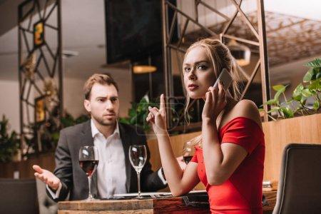 Photo pour Homme insatisfait regardant petite amie parler sur smartphone pendant le dîner - image libre de droit