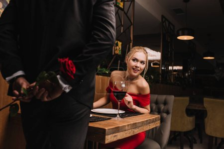 curious girl looking at man hiding red rose in restaurant