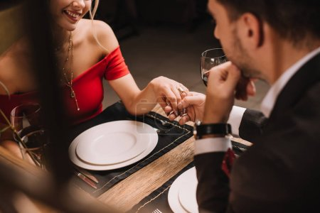 Photo for Cropped view of couple holding hands in restaurant during dinner - Royalty Free Image