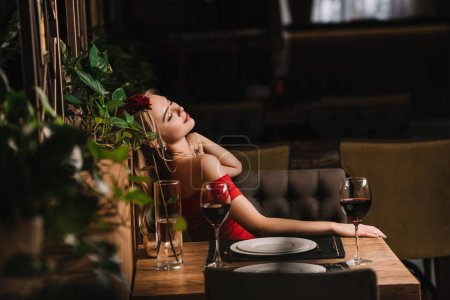 Photo for Beautiful woman sitting in red dress in restaurant - Royalty Free Image