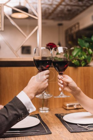 Photo for Cropped view of couple clinking with glasses of red wine during romantic date - Royalty Free Image