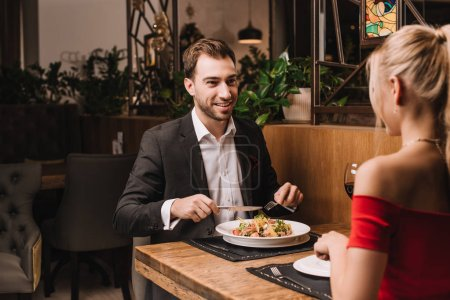 Photo for Handsome man having dinner with girlfriend in restaurant - Royalty Free Image