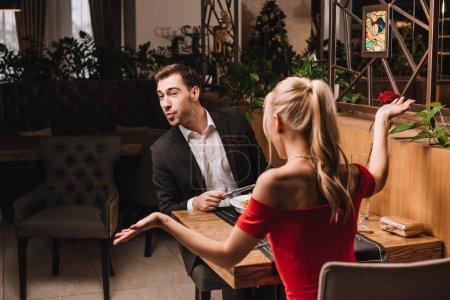 Photo pour Homme surpris assis au restaurant avec femme blonde - image libre de droit