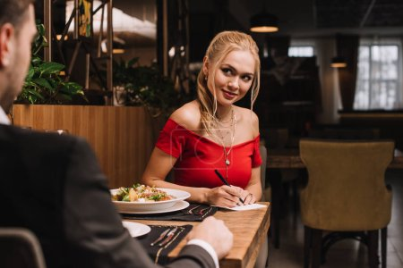 attractive blonde woman writing on paper while looking at boyfriend in restaurant
