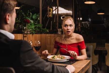 shocked woman looking at boyfriend while holding cutlery near salad in restaurant