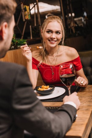 cheerful woman holding spoon with sweet dessert and looking at boyfriend in restaurant