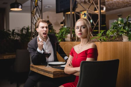 selective focus of offended woman sitting with crossed arms near screaming boyfriend in restaurant