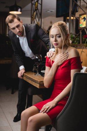 selective focus of blonde woman sitting upset near worried boyfriend in restaurant