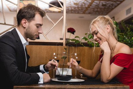 Photo for Happy couple sharing dessert while sitting in restaurant - Royalty Free Image