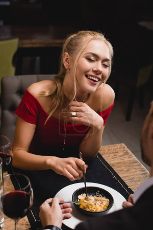 happy woman laughing  near boyfriend while sharing dessert in restaurant
