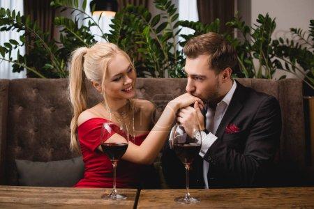 Photo pour Bel homme baisant la main d'une femme attrayante au restaurant pendant la date romantique - image libre de droit