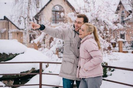 Photo pour Bel homme debout avec une copine blonde et pointer avec le doigt - image libre de droit